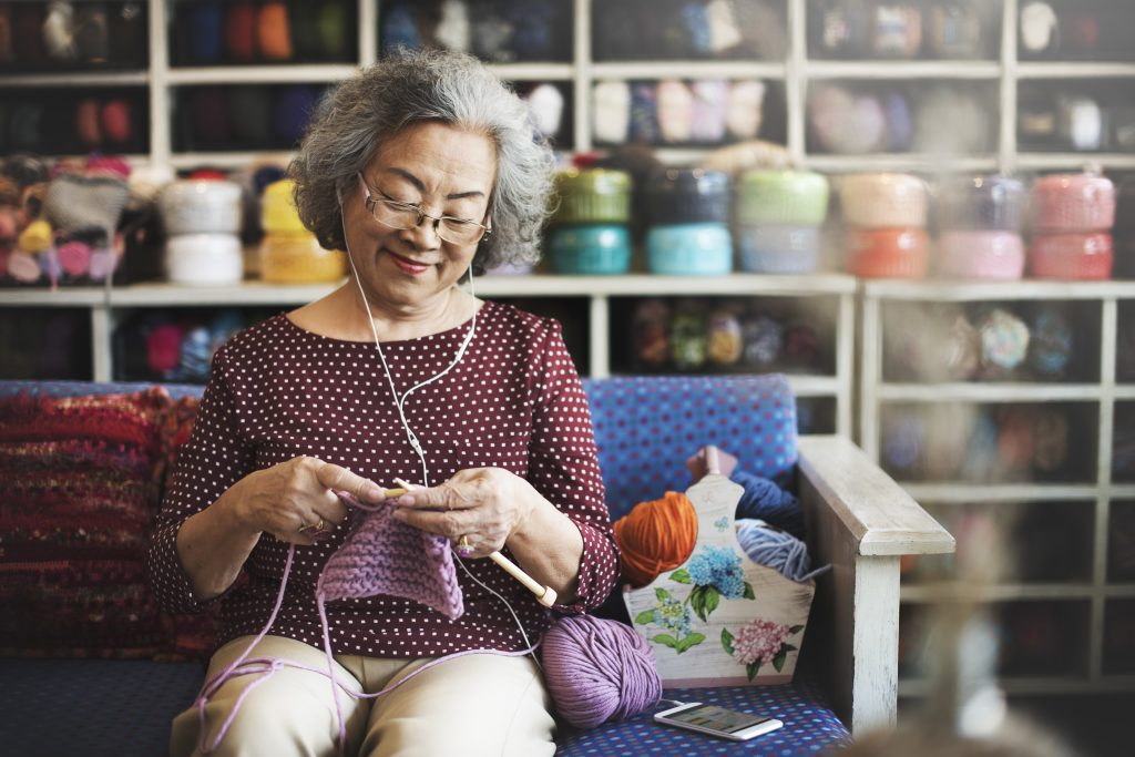 Retired lady smiling, listening to music and knitting