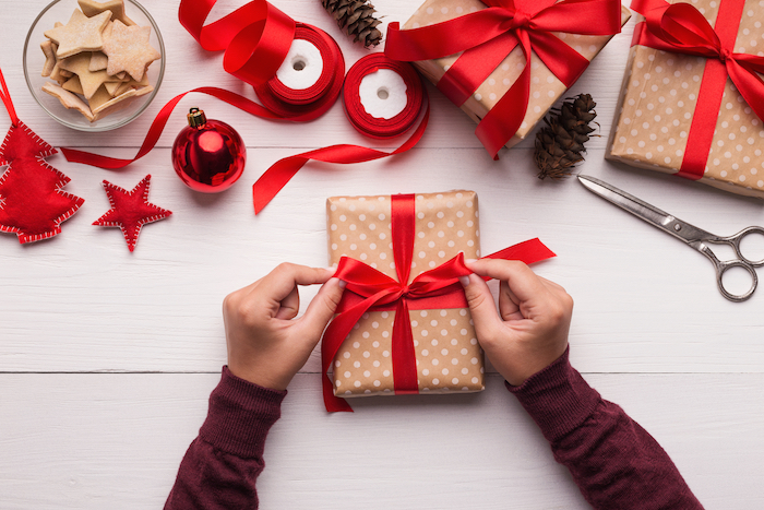 Person wrapping Christmas presents, tying a ribbon.