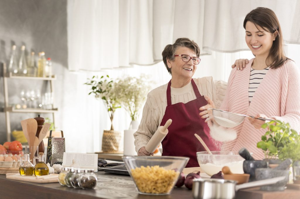 Elderly lady and young lady baking together, laughing.