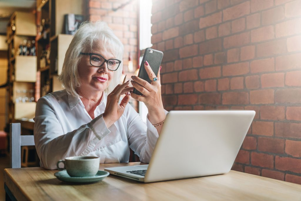Senior lady sitting at a table with her phone and laptop