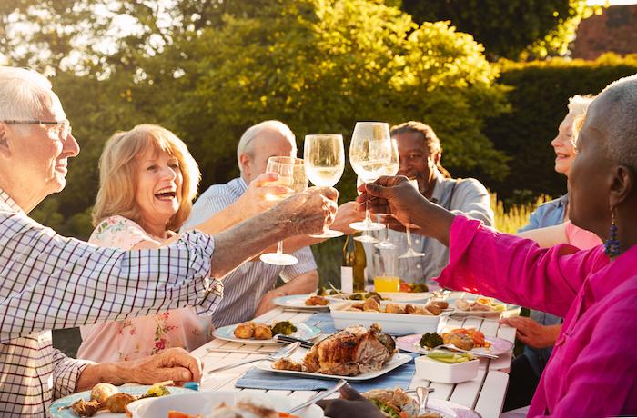 Elderly group of friends enjoying outdoor feast together.