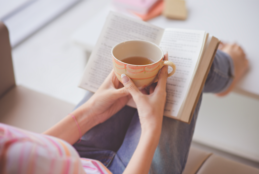 self care - lady reading a book with a cup of tea