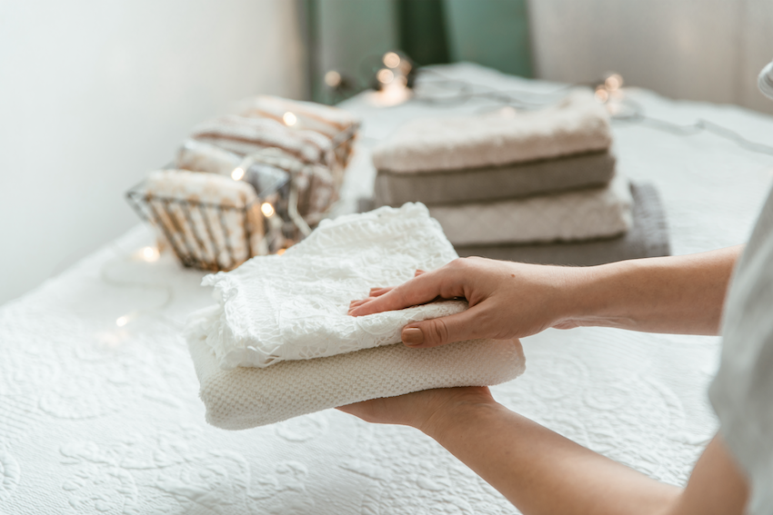 Best home decluttering tips: woman folding towels at home