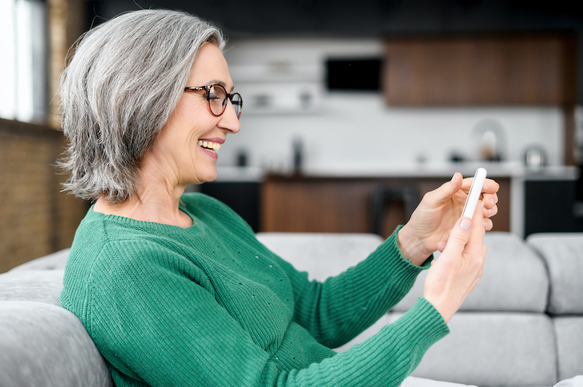 retired lady smiling and using her phone at home